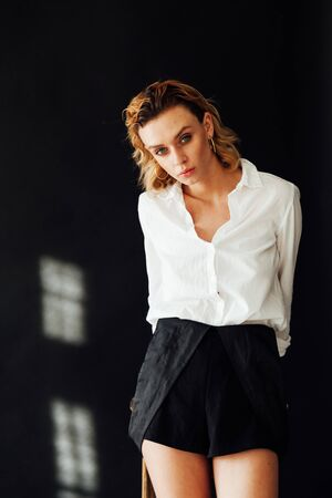 Portrait of a beautiful fashionable blonde woman in a black jumpsuit with a white shirt