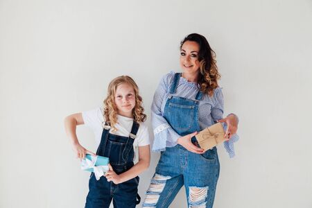 Mom with little girl in denim jumpsuit holding gifts