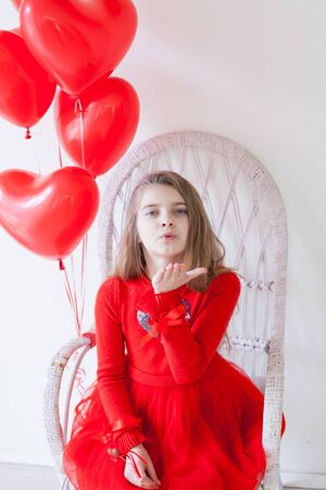 Beautiful little girl with red balloons in the shape of a heart at the holiday Stock Photo