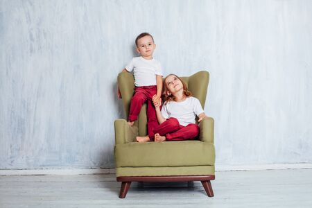 boy and girl are brother and sister sitting in green Chair