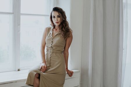 Portrait of a beautiful fashionable woman in a beige stylish dress
