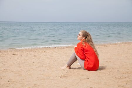 Beautiful blonde woman on an empty beach by the sea sits on the sand