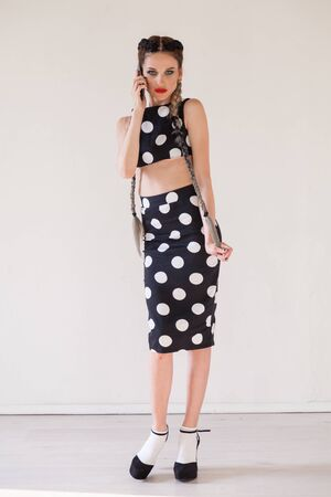 Portrait of a beautiful fashionable woman with braids dress in polka dots