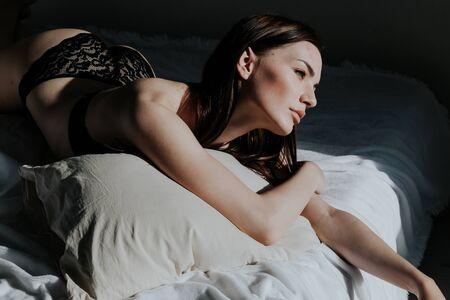 mujer en ropa interior se acuesta en la cama en el dormitorio por la mañana Foto de archivo