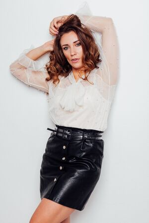 portrait of a beautiful fashionable woman with hair curls in a white blouse and black skirt