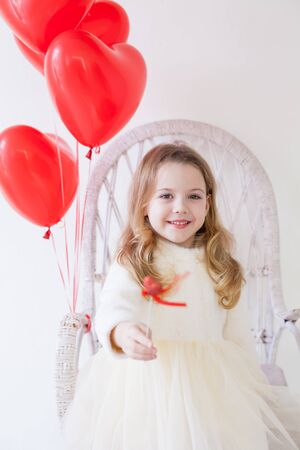 Beautiful fashionable little girl with red balloons in the shape of a heart at the holiday