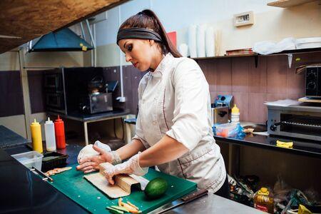 femme chef prépare des sushis frais dans la cuisine du restaurant