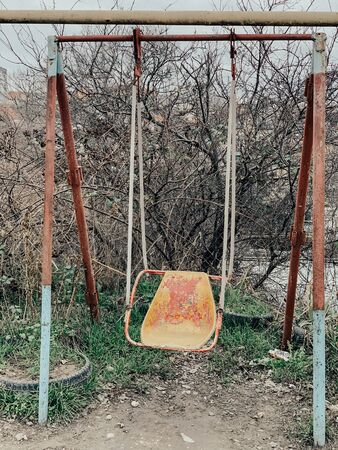 Old vintage rusty baby swing abandoned