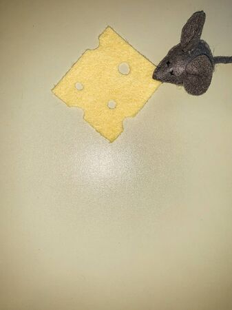 mouse toy with yellow cheese on a grey background 版權商用圖片