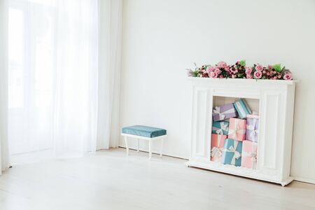 fireplace with flowers and gifts in a white room