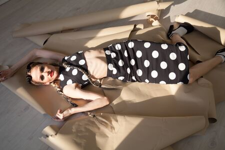 Portrait of a beautiful fashionable woman with braids in a dress in white polka dots Reklamní fotografie