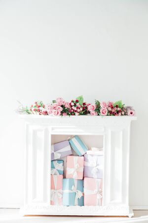 fireplace with flowers and gifts in the interior of the white room