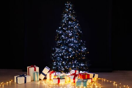 Christmas tree with gifts lights garlands for the new year on a black