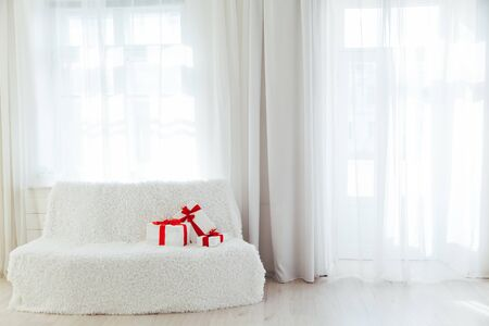 white sofa with gifts in the interior of the white room with windows