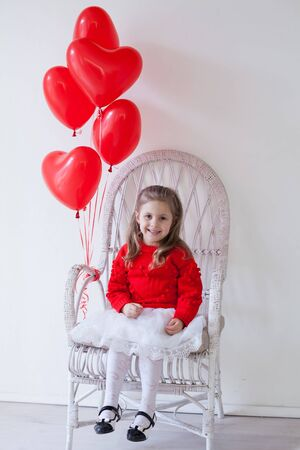 little beautiful girl on holiday with red heart-shaped balloons Stock Photo