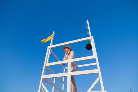 fashionable blonde woman lifeguard on the beach by the sea