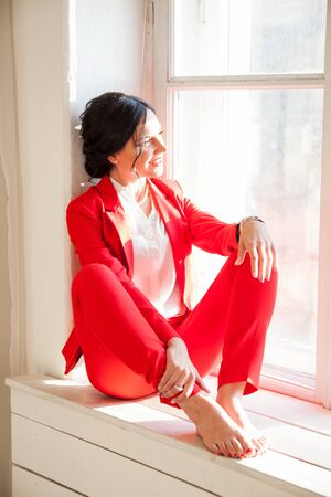 Portrait of a business woman brunette in a red business suit by the window