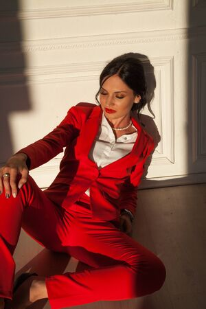 Portrait of a business woman brunette in a red business suit in the office