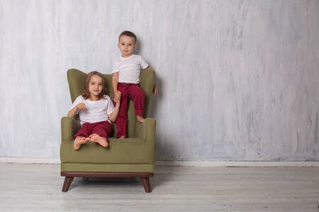 little boy and girl sitting in a green chair in the room