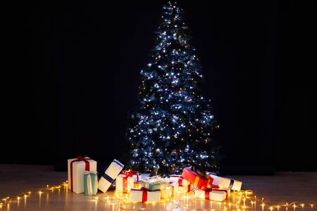 Christmas tree with gifts and lights garlands new year background