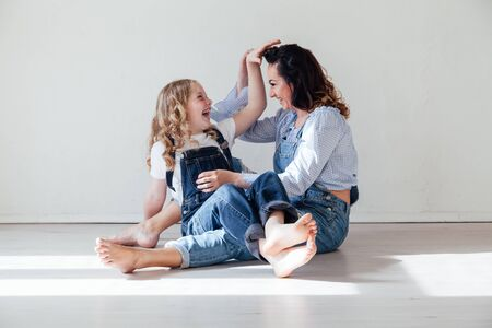 Happy moms family with daughter on the floor