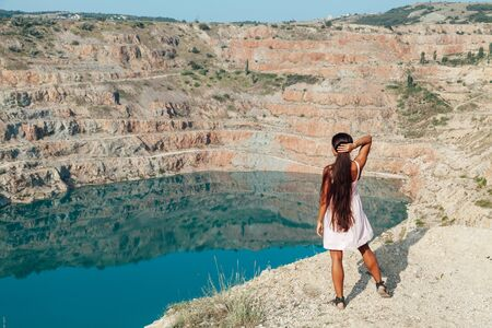 Beautiful woman with long hair in dress looks at the landscape of the lake