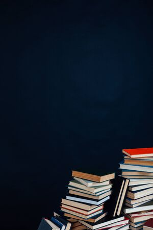 many stacks of educational books in the university library on a black background Stockfoto