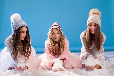 Three beautiful fashionable girls in winter cap snow Stock Photo