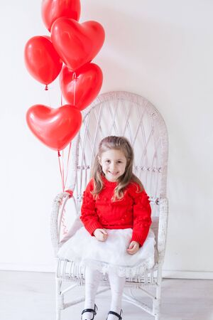 Beautiful little girl with red balloons in the shape of a heart