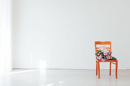 chair with flowers in the interior of an empty room