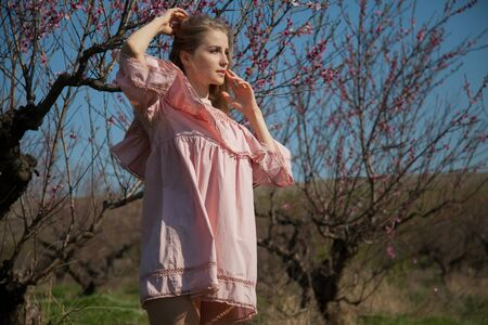 Beautiful blonde woman in pink dress collects flowers in flowering garden