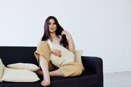 portrait of a beautiful fashionable oriental woman on the couch in home