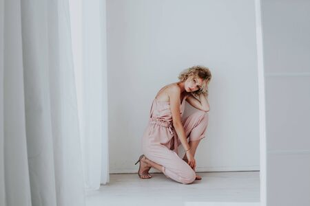 Beautiful fashionable blonde woman in pink clothes poses in white room 免版税图像
