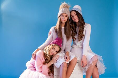 Portrait of three beautiful fashionable girls in winter hats with snow