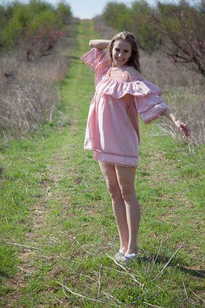 Beautiful blonde woman in pink dress walks through the flowering garden in the spring Stok Fotoğraf