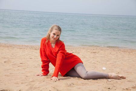Beautiful blonde woman sits on a beach alone