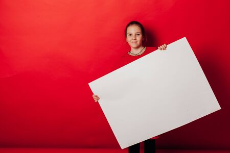 Schoolgirls girl holds sign for inscriptions on red background