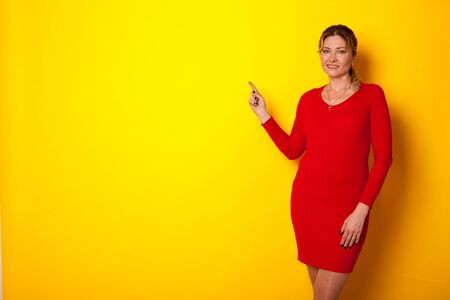 woman forty years in a dress on a yellow background