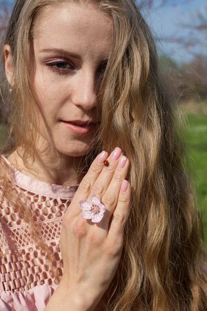 Beautiful blonde woman in pink dress and ladybug insect