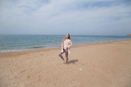 Beautiful blonde woman walks on the sea beach alone