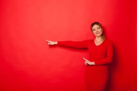 woman forty years in a dress on a red background Stok Fotoğraf
