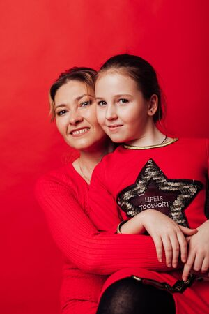 Mom and daughter lovingly cuddle on a red background