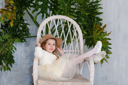 Beautiful little girl in white dress sits in vintage chair