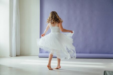 Beautiful little girl in dress dances alone at home