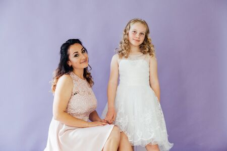 beautiful mom and daughter in white dresses in close family