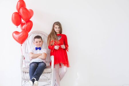 Boy and girl friends on holiday with red balloons