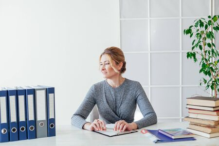 beautiful business woman sits at desk with teachers books