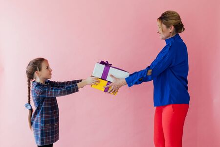 Mom and daughter family give each other gifts on a pink background