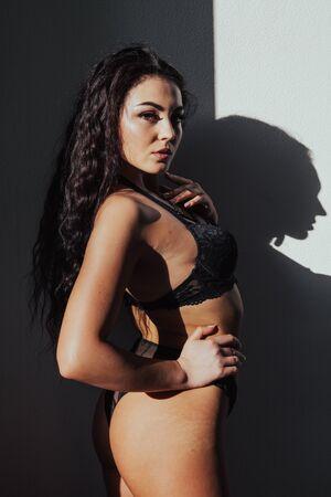 Beautiful young brunette woman in black lingerie in sunlight Stok Fotoğraf