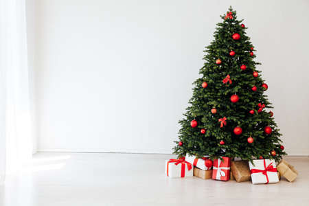 The interior of the white room is a green Christmas tree with red gifts for the new year decor winter